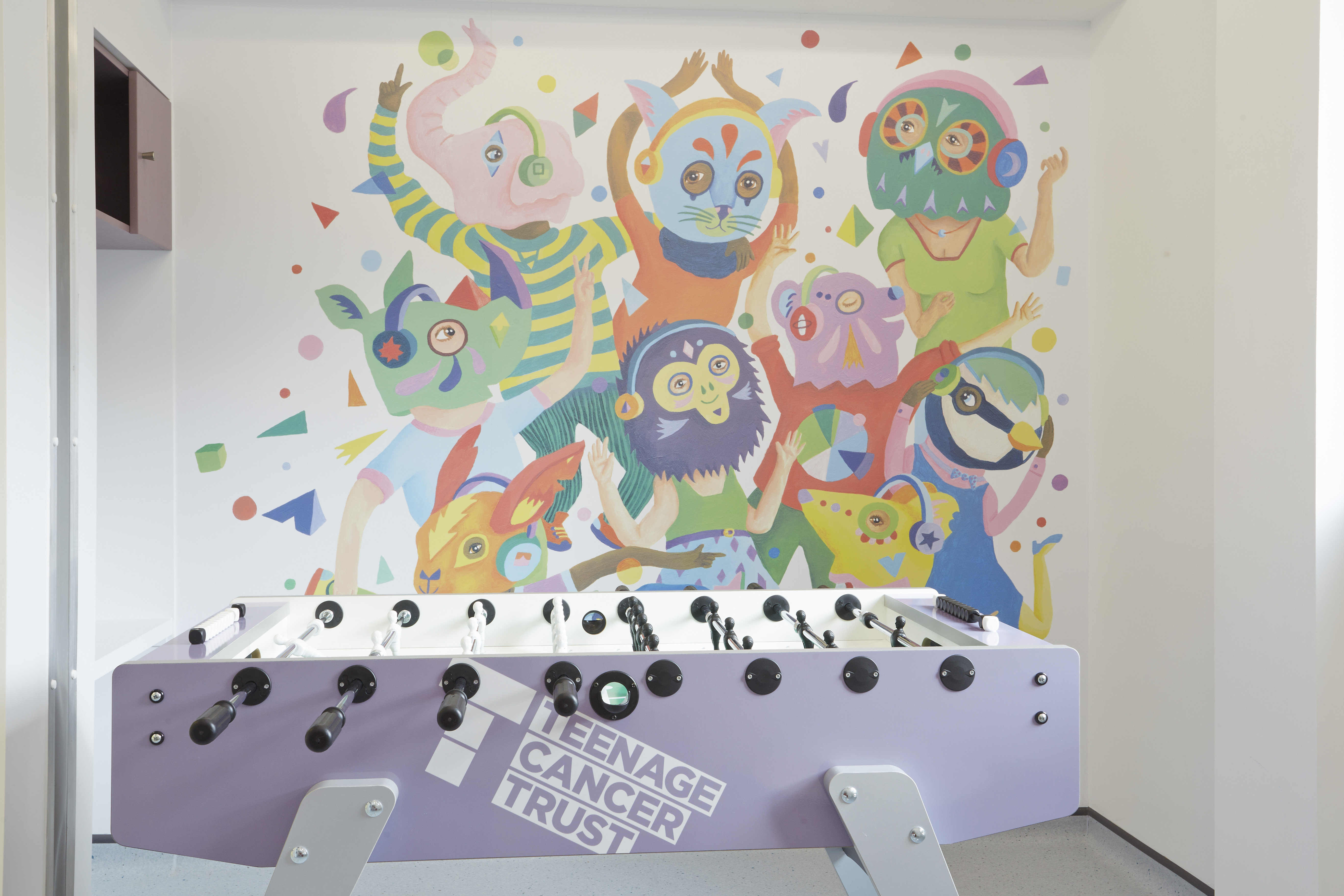 Illustrator Dave Bain created a colourful wallwork for the social space in Teenage Cancer Trust unit